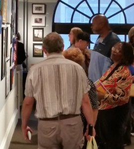 A group of gallery attendees view the mental wellness programs art on the walls at Vision 2015