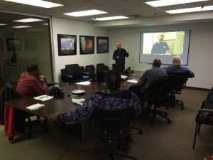 A group of people in a conference room gather for a jobs training program
