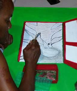 A member of the CHOICE Art Group works on a pencil and marker sketch on paper with a colorful red border