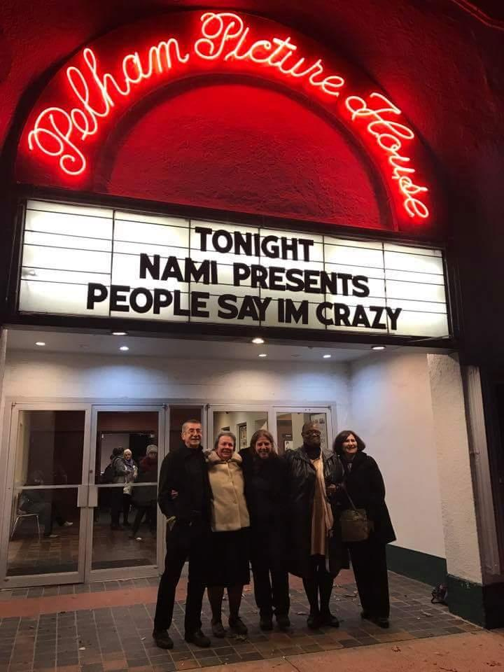 A group of CHOICE advocated pose for a photo outside the Pelham Picture Movie House under the marquee for the film, People Say I'm Crazy