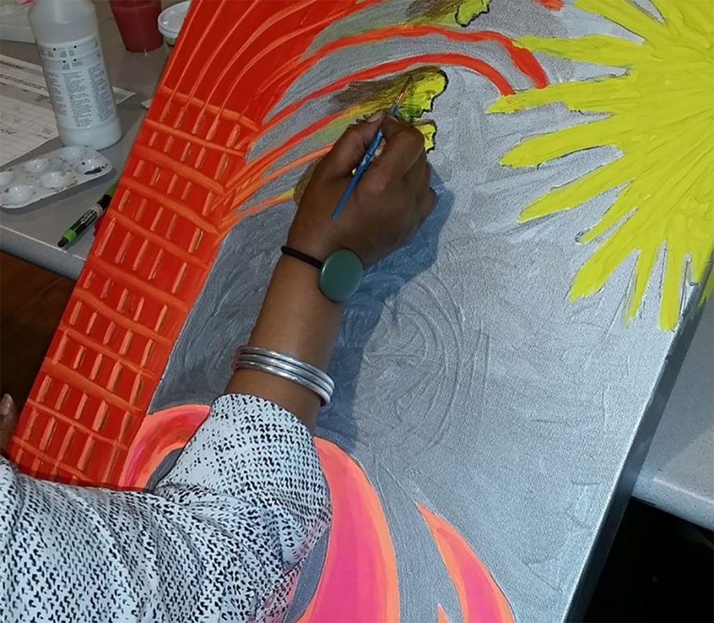 A woman paints a yellow and red starburst at an art socialization group