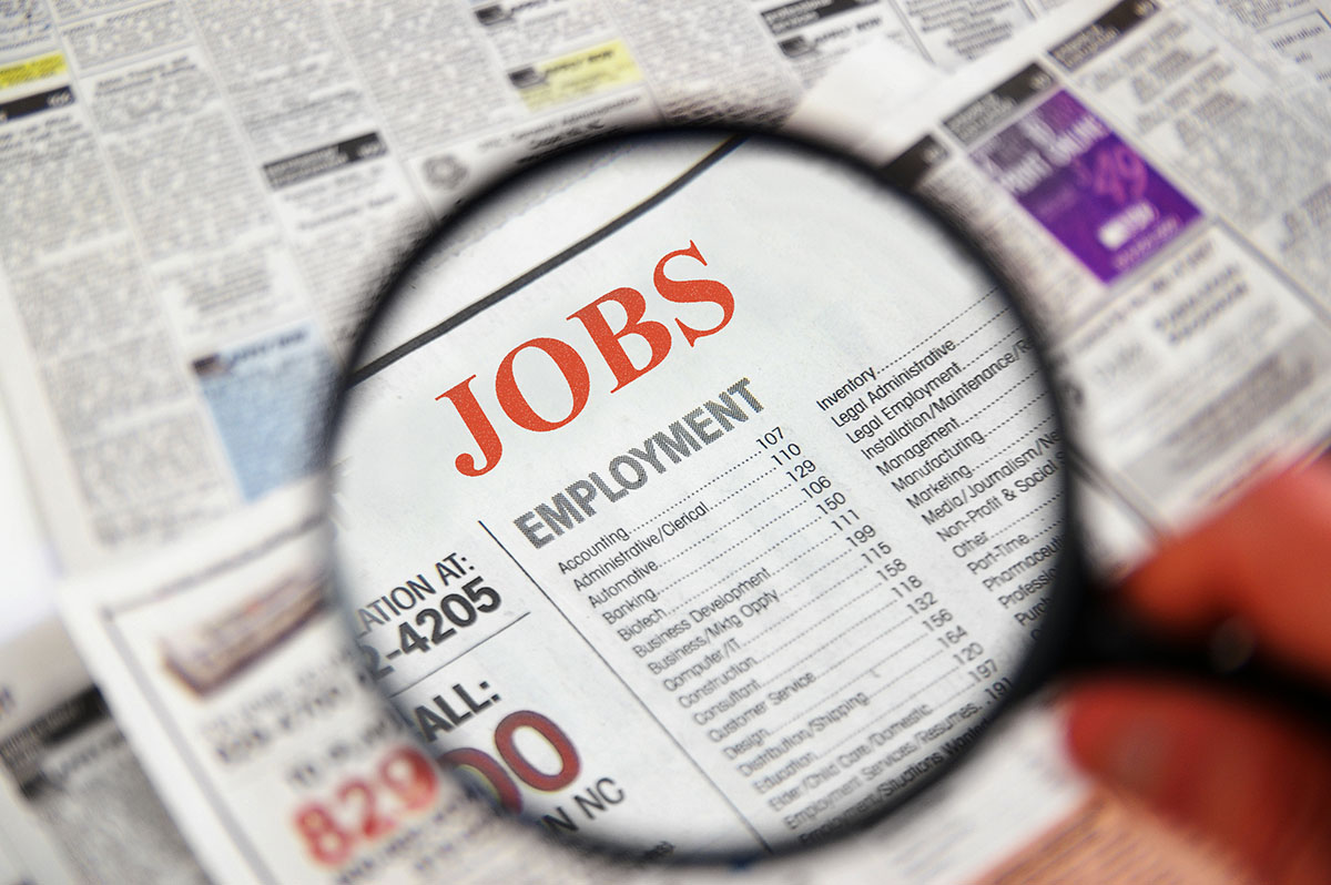 A newspaper showing job search ads with a magnifying glass