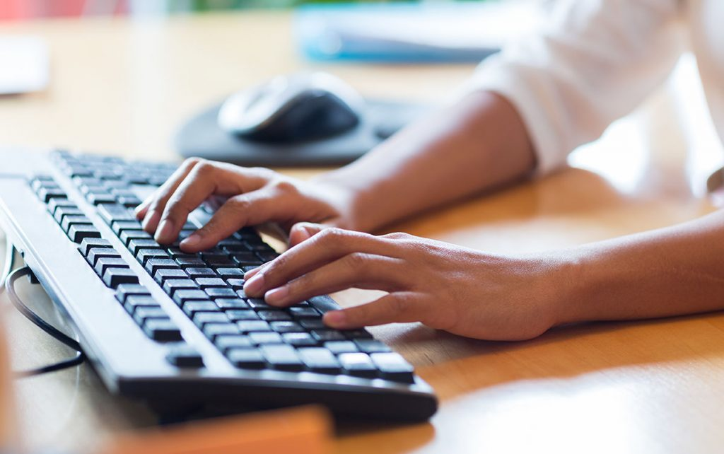 Close up of a woman typing on a keyboard